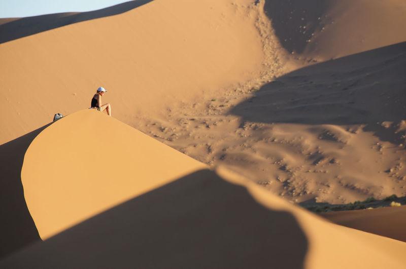 Person sitting on sandy desert