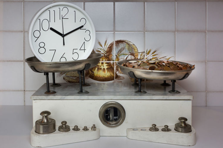 Close-up of clock and coins on weight scale