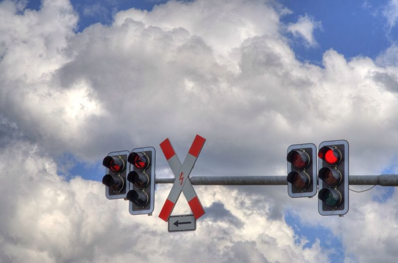Low angle view of traffic signal against cloudy sky