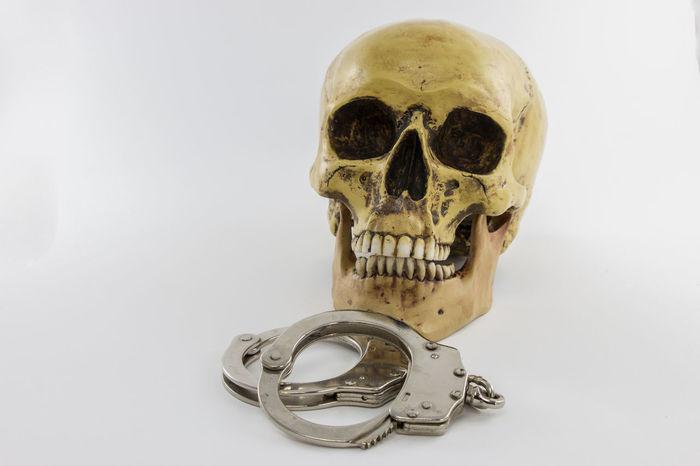 Skull with handcuffs on white background Human Skeleton Human Skull Studio Shot White Background Skull Handcuffs  Crime Arrest Criminal Prison Violence Death Dead Murderer Killer Cuffs