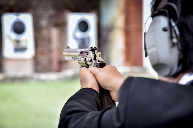 Midsection of man aiming gun during target shooting