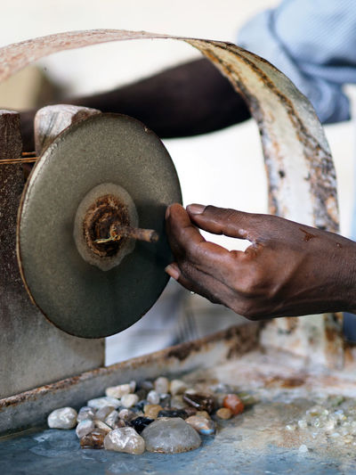 Cropped image of hand working on machine