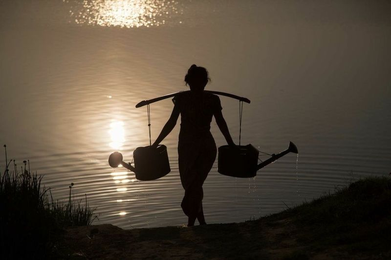 Silhouette woman carrying watering cans by sea