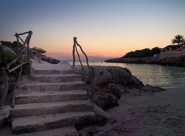 steps leading down to a beach at twilight with a glowing evening sky reflected in a calm dark sea and surrounding cliffs Sky Sunset Staircase Tranquil Scene Beauty In Nature Nature Tranquility Water Scenics - Nature No People Sea Architecture Steps And Staircases Built Structure Outdoors Rock Railing Non-urban Scene Beach Bay Of Water Ciutadella Travel Minorca