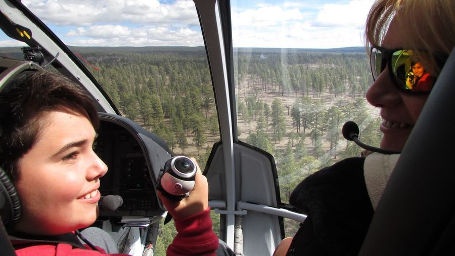 Rear view of happy woman and boy in helicopter over landscape