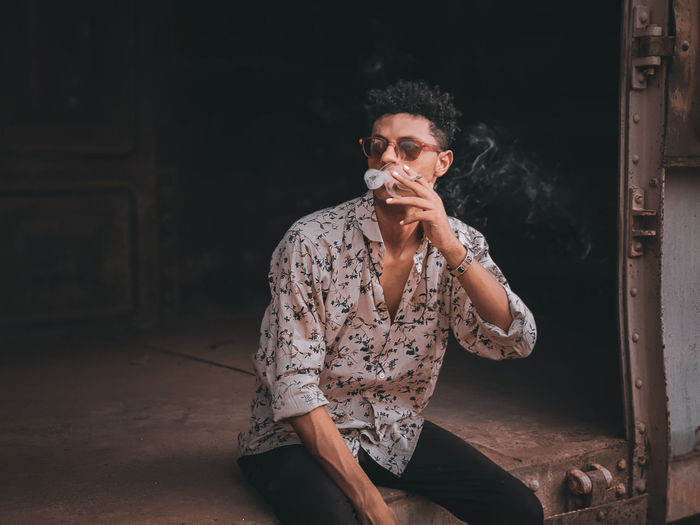 Young man smoking a cigarette in a train