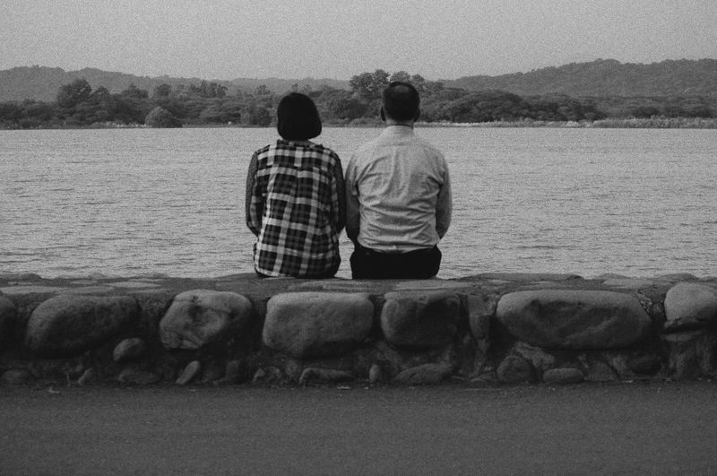 Rear view of couple sitting on retaining wall against sea