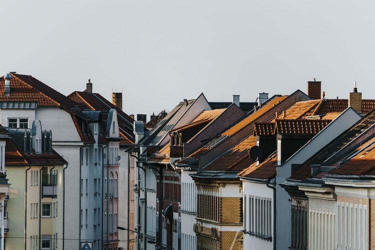 Rooftops with chimneys in city against clear sky