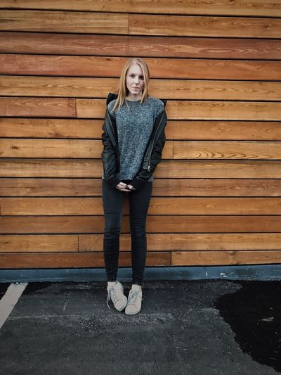Full length portrait of young woman standing against wooden wall