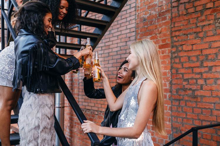 Friends toasting drinks while standing on staircase