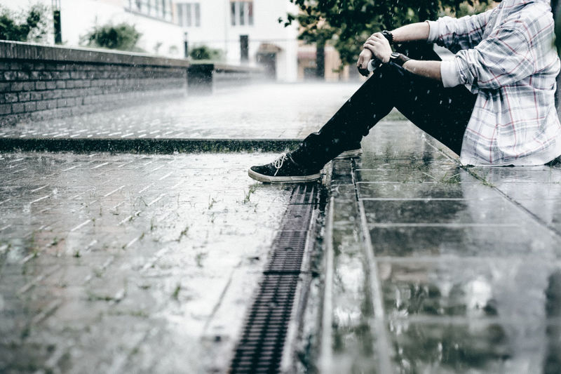 Low section of young man sitting on footpath during rain