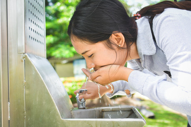 Close-up side view of young woman drinking water