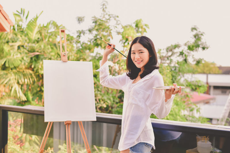Beautiful Woman Casual Clothing Day Easel Focus On Foreground Front View Holding Leisure Activity Lifestyles Nature One Person Outdoors Plant Real People Sitting Standing Table Three Quarter Length Women Young Adult Young Women