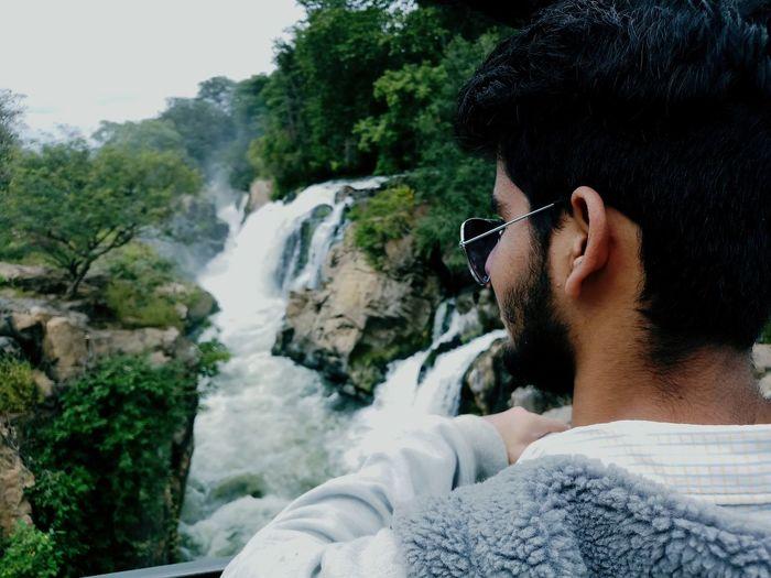 Close-up of young man looking at waterfall