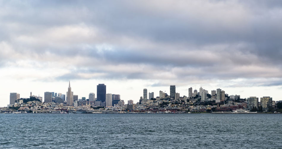 View from the sea of San Francisco skyline and its bay in a cloudy day of summer. American cityscape with skyscrapers and a sky full of dark clouds American Area Business California Downtown Skyline USA America Architecture Bay Building City Cityscape Clouds District Financial Outdoors Sand Sea Sky Skyscraper Town Urban Water Waterfront