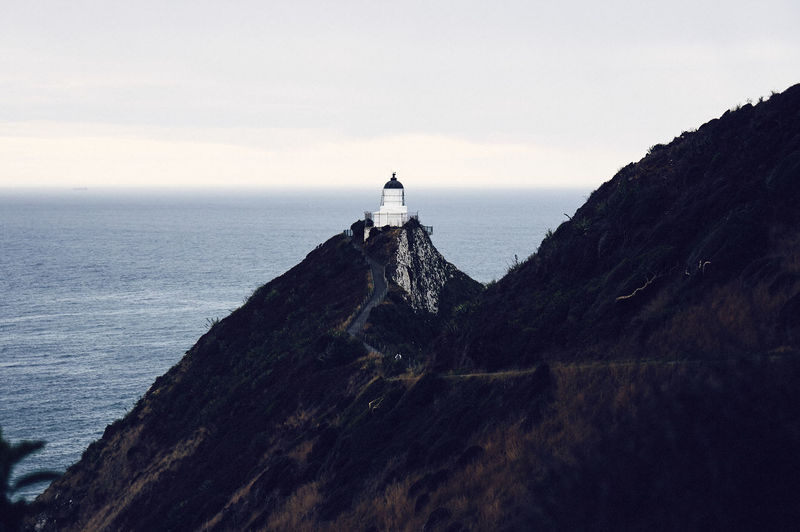 Lighthouse on mountain by sea against sky