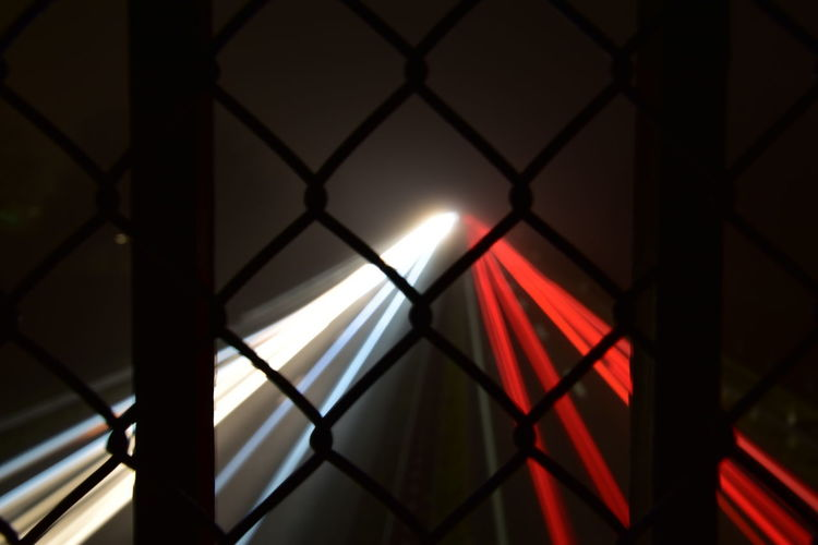Close-up of illuminated lights seen through chainlink fence