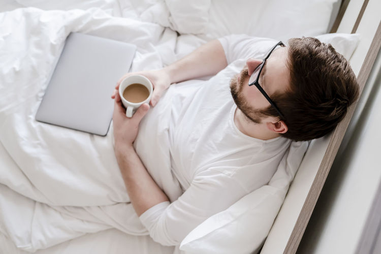 High angle view of man holding coffee cup on bed