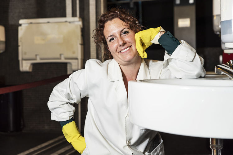 Portrait Smiling One Person Adult Indoors  Looking At Camera Occupation Front View Emotion Mature Adult Women Working Hairstyle Uniform Maid Cleaning Equipment Cleaning Product Cleaning Yellow Gloves Cleaning Woman White Coat White Wrapper Happy At Work