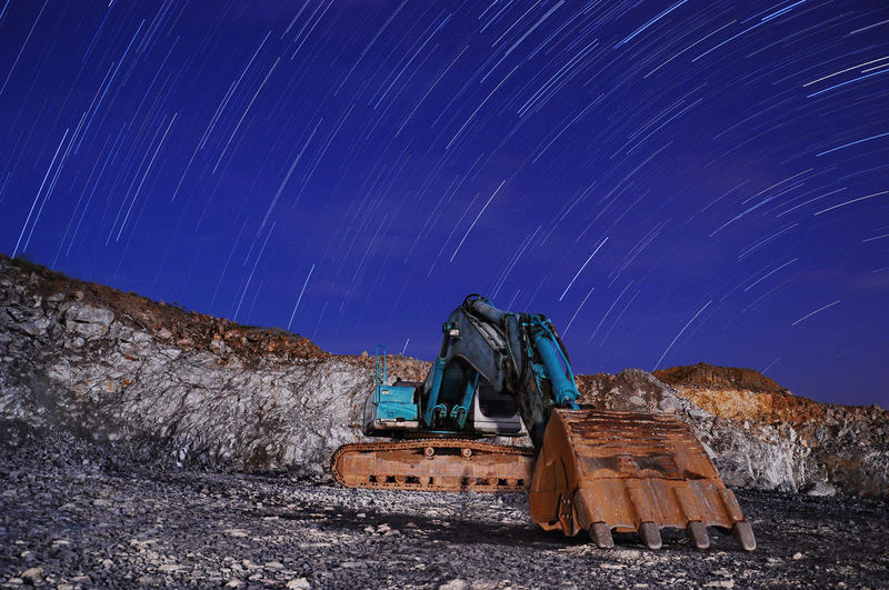 Bulldozer On Field Against Star Trails On Sky At Night