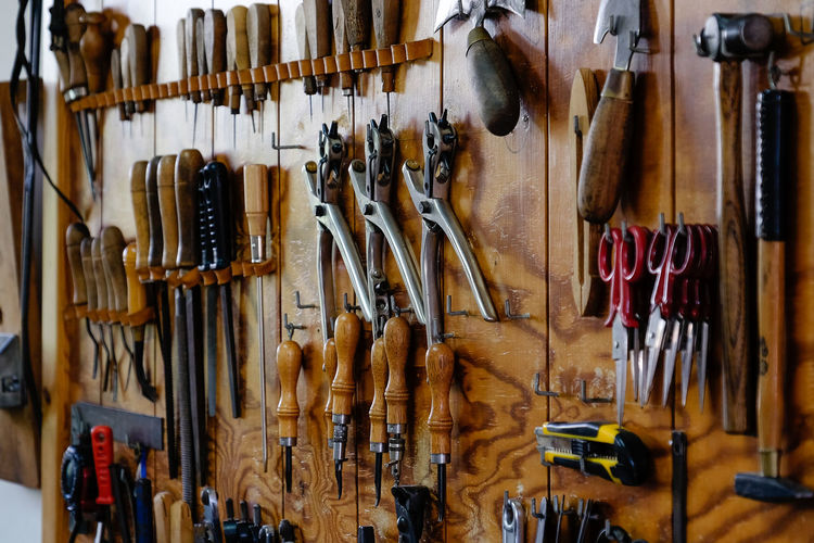 Hand tools on wooden wall at workshop