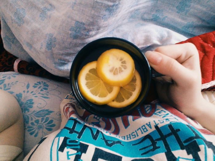 Directly above shot of woman holding cup of lemon tea