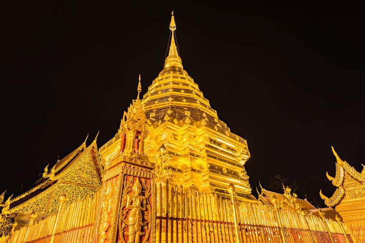 Low angle view of illuminated temple building against sky at night