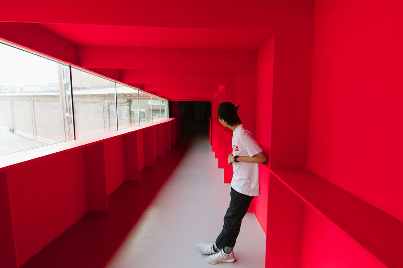 Red Dimension Bright EyeEm Best Shots Lost Wanderlust Adult Architectural Column Architecture Bold Building Built Structure Casual Clothing Day Full Length Indoors  Lifestyles One Person Real People Rear View Red Standing Wall - Building Feature Women