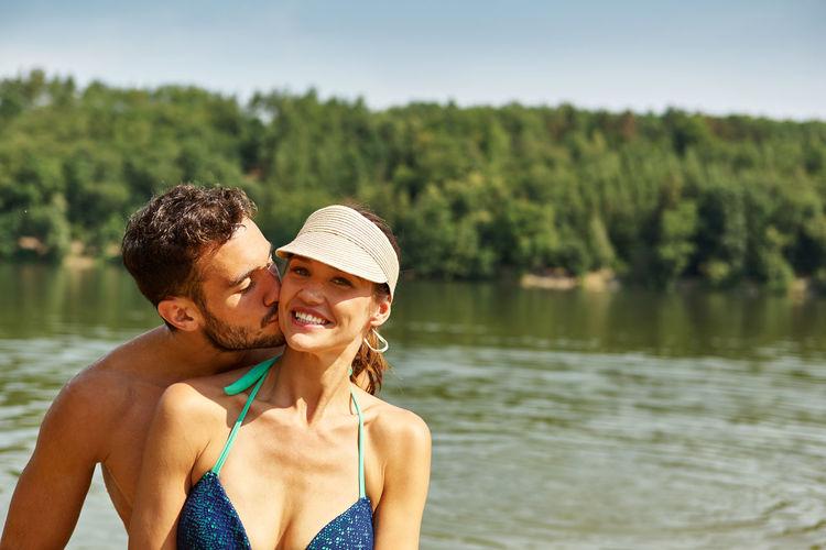 Man kissing smiling woman against lake
