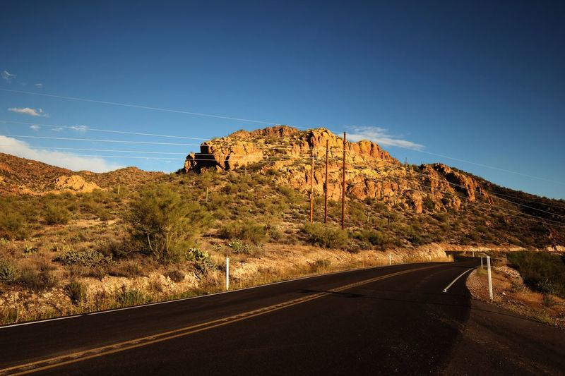 Winding open road in Phoenix Arizona Rock Formation Road Asphalt Vacation Freedom Sky Mountain Nature Road No People Environment Beauty In Nature Blue Tranquil Scene Tranquility Scenics - Nature Landscape Clear Sky Transportation Sunlight The Way Forward Rock - Object Plant Non-urban Scene Rock