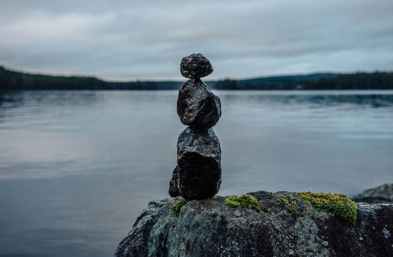 Close-up of statue on rock by lake against sky