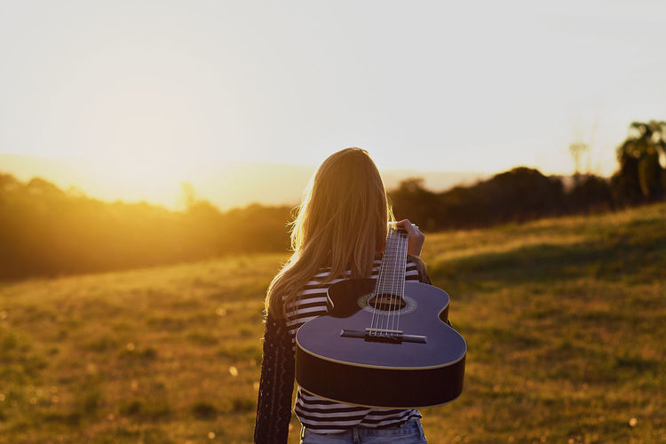 Rear view of woman with guitar on field