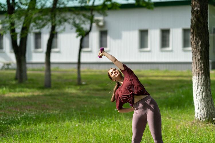 Full length of woman holding umbrella on field