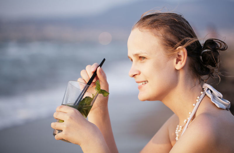 Close-Up Of Beautiful Woman Having Mojito At Beach