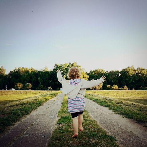 Rear view of girl walking on field against clear sky