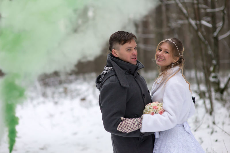 Beautiful Woman Bouquet Bride Cold Temperature Day Flower Green Smoke Happiness Holding Leisure Activity Lifestyles Love Outdoors Real People Smiling Snow Standing Togetherness Traditional Clothing Two People Wedding Dress Winter Young Adult Young Men Young Women