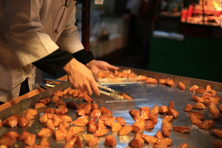 Midsection of chef packing food in restaurant