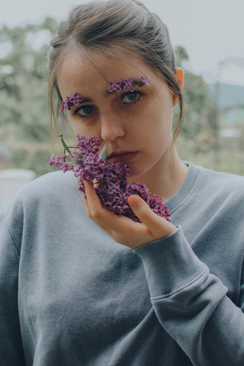 Portrait of a young woman holding lilac flowers plant