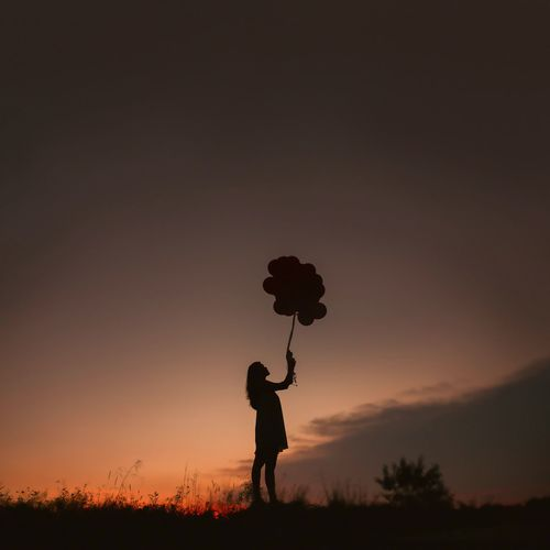 Silhouette Of Young Woman Holding Balloons