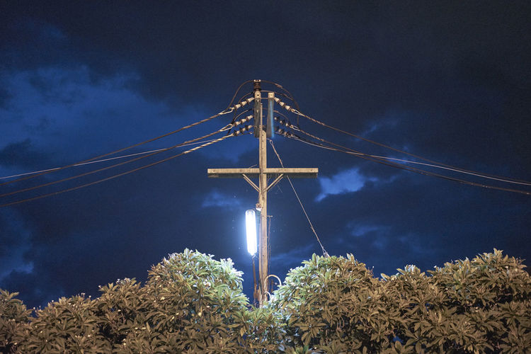 Low angle view of power line against cloudy sky at night
