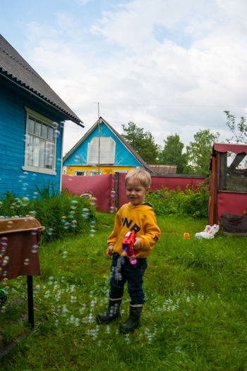 Boy standing by plants against sky
