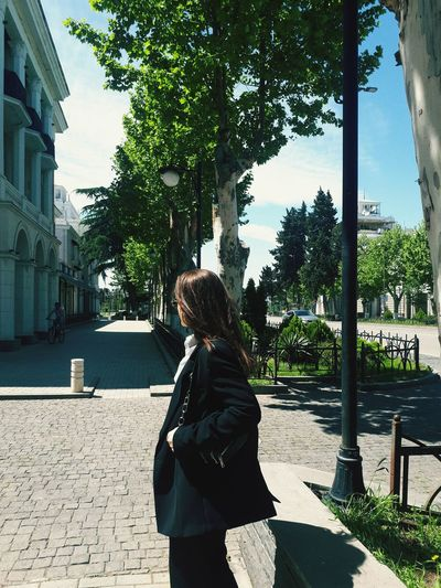 Rear view of woman standing against trees in city