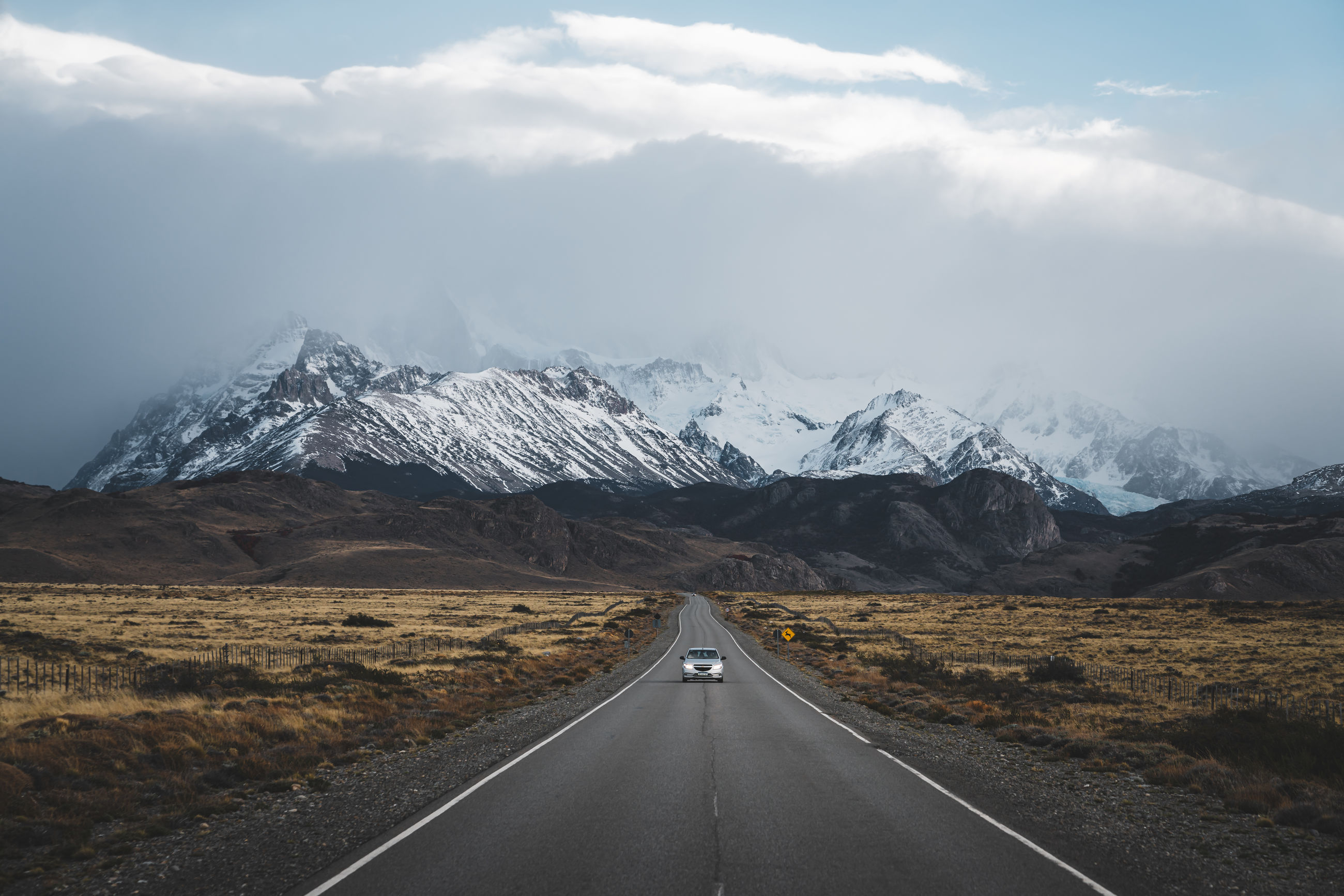 road, mountain, transportation, direction, the way forward, symbol, beauty in nature, snow, landscape, sky, environment, road marking, marking, mountain range, cold temperature, scenics - nature, cloud - sky, diminishing perspective, winter, no people, snowcapped mountain, outdoors, mountain peak, dividing line
