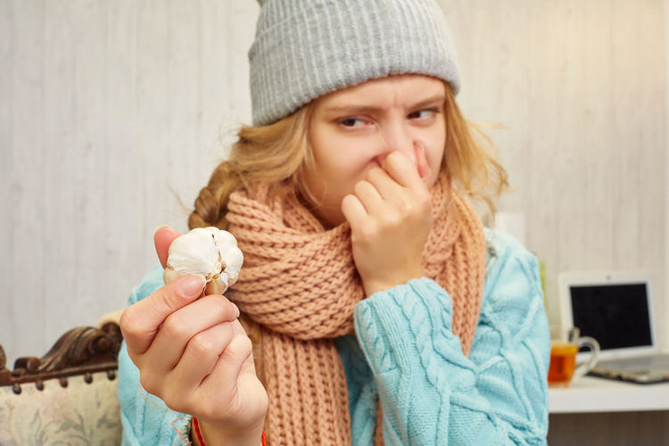 Portrait of woman holding ice cream in winter