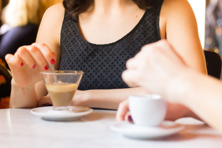 Drink Food And Drink Refreshment One Person Women Real People Table Midsection Food Front View Adult Drinking Glass Glass Holding Drinking Bar Coffee Coffee - Drink Coffee Cup Coffee Time Coffe Break  Cafe Caffeine Breaktime Hand Indoors  Freshness Leisure Activity