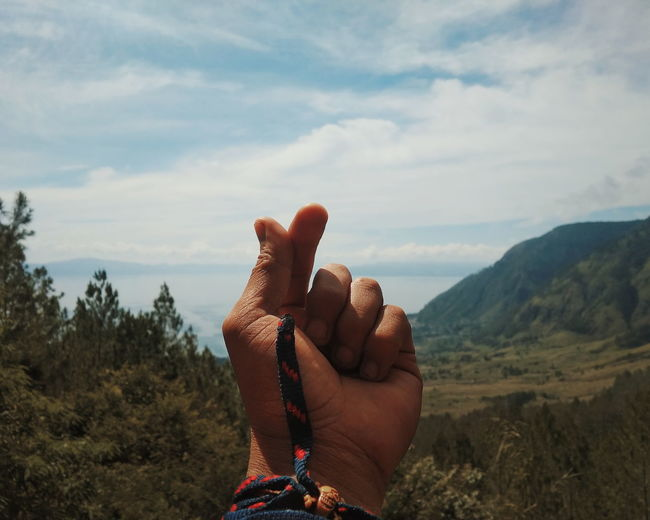 Cropped hand with mountains in background against cloudy sky