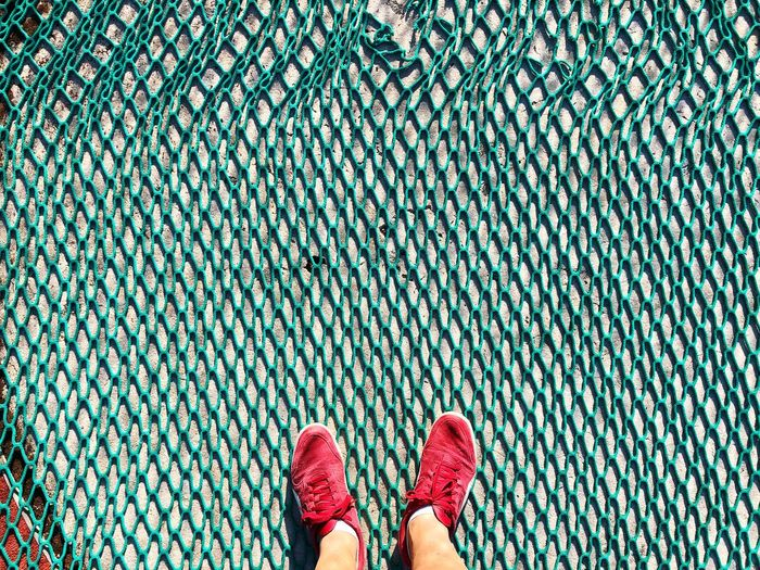 Low section of person standing on net