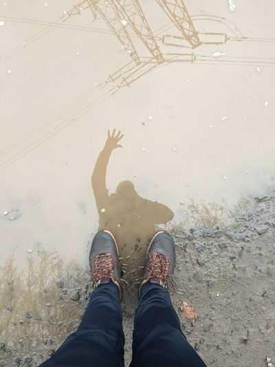 Low Section Of Person Reflection With Electricity Pylon In Puddle