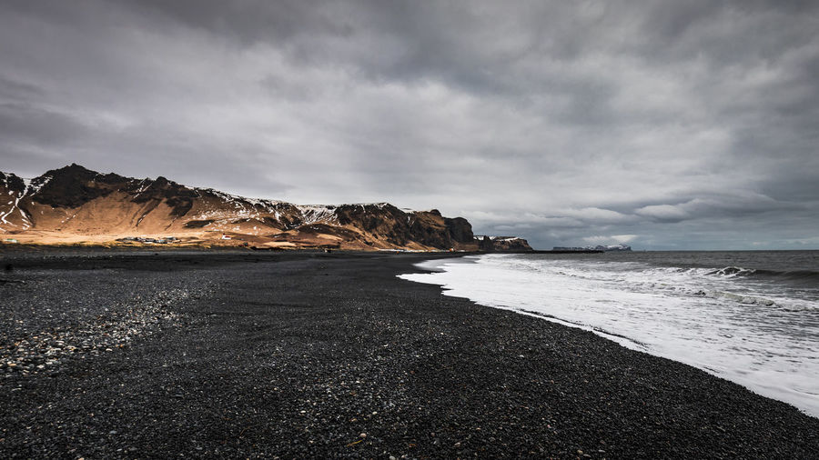 overview of the black sand beach in iceland Iceland Nature Travel Vík í Mýrdal Beach Beauty In Nature Black Sand Beach Iceland Blacksandbeach Cloud - Sky Iceland Trip Idyllic Land Nature Non-urban Scene Outdoor Overcast Rock Rock - Object Scenics - Nature Sea Sky Solid Travel Destinations Traveliceland Water