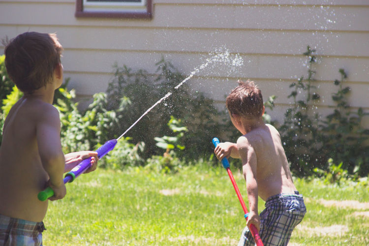 Children playing with water in yard